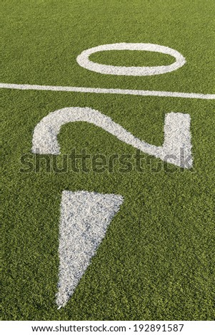 The twenty-yard mark on the floor of a football stadium. - stock photo