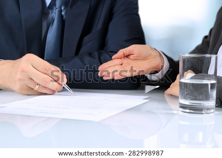 The Two business partners signing a document - stock photo