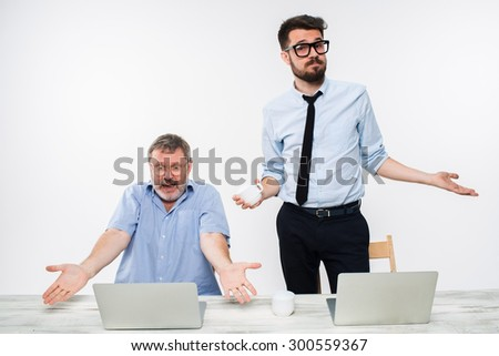 The two colleagues working together at office on white  background. Old man sitting at the table with computers and both shruging aside as if to saying -It happened - stock photo