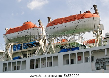 the two orange lifeboats on a ferry - stock photo