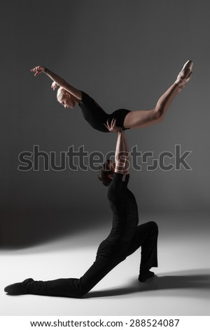 The two young modern ballet dancers in black suits posing over gray studio background  - stock photo