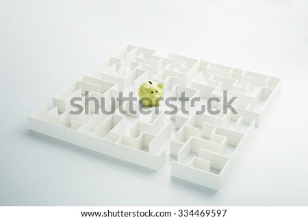 The uncertainty of money and business. Piggy bank hidden inside a maze - stock photo