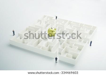 The uncertainty of money and business. Piggy bank hidden inside a maze - stock photo