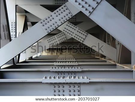 The underside of a bridge with large steel girders, bolts and nuts  - stock photo