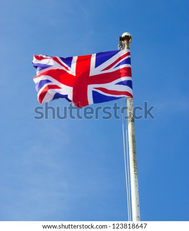 The Union Jack Flag flying from a Flagpole against blue sky. National flag of Great Britain and Northern Ireland - stock photo