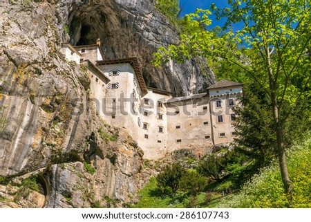 The unique and famous Predjama Castle in Slovenia. The renaissance castle was built within a cave mouth to offer best protection. - stock photo