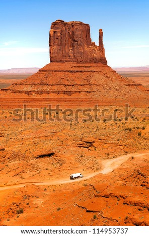 The unique landscape of Monument Valley, Utah, USA. Small truck in foreground, (identifying features removed), gives perspective and scale to the Butte. - stock photo