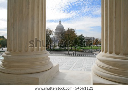 The United States Capitol building viewed from the marble columns of the Supreme Court. - stock photo