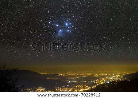 The Universe above city lights. The Pleiades star cluster. - stock photo