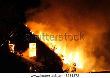 The upper floor of an urban house on fire in the night - stock photo