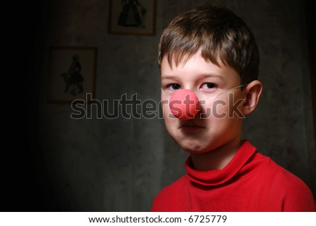 The upset boy with clown's nose in dark room - stock photo