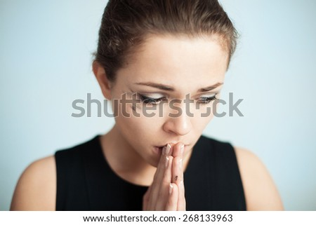 the upset woman with running mascara prays - stock photo