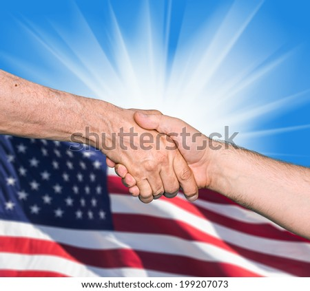 The USA flag and shaking hands of two male people on blue sky background - stock photo