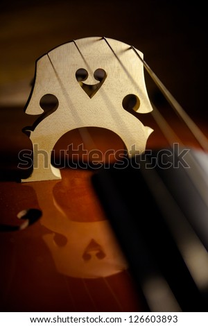 The Valentine heart-shaped woodwork in the bridge of a string bass reflected in the body of the instrument. - stock photo