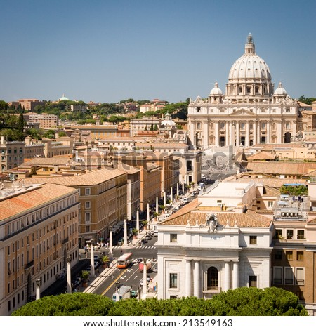 The Vatican City. An elevated view looking over  the rooftops of the Vatican City on the main approach to St. Peter's square and the Basilica in the distance. - stock photo