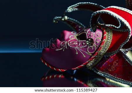 The Venetian mask with bells on a mirror table - stock photo