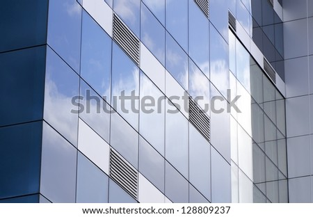 The ventilation grids,exterior facade of building covered with glass reflections of the clouds taken.ventilation grills to be emphasized in this photograph and the glass-clad building on the original - stock photo