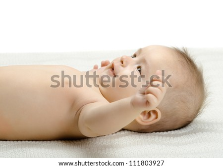 the very beautiful fun little baby ,  lie on light bedding - stock photo