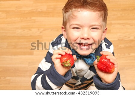 The very handsome, cute and clever boy dressed in classical style clothes looking up and holding a strawberry and smile very much.  - stock photo