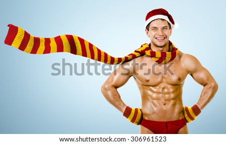 the very muscular  bronzed handsome sexy Santa Claus in striped red-yellow  muffler, smile, on light blue background - stock photo