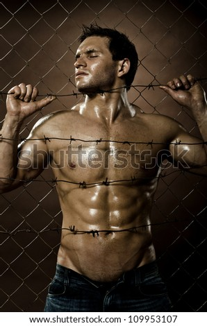 the very muscular handsome felon guy , misery  out of netting   steel fence with  barbed wire - stock photo