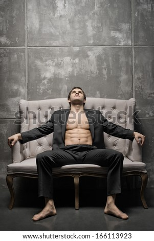 the very muscular handsome sexy guy in black  suit indoor - stock photo