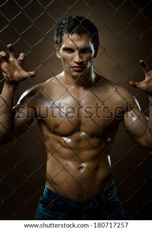 the very muscular handsome sexy guy, on netting steel fence - stock photo