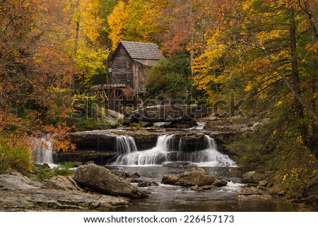 The vibrant colors of Autumn surround the old grist mill at Babcock State Park in West Virginia. - stock photo
