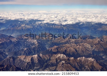 The view from the airplane window at alps mountains and clouds   - stock photo