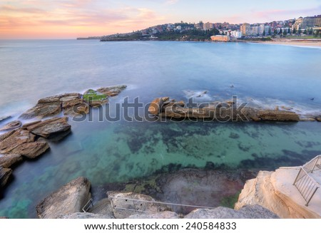 The view from the headland down into Giles Baths rockpool at Coogee in a mid tide.  At low tide the rockshelf at bottom of stairs will become exposed.  Long exposure taken at sunrise.   - stock photo