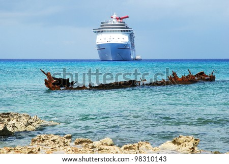 The view of a sunken ship with a cruise liner in a background on Grand Cayman island (Cayman Islands). - stock photo