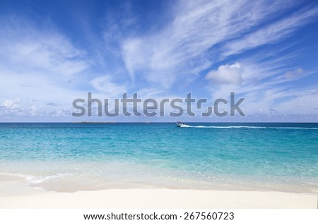 The view of Caribbean Sea with motorboat passing by (Paradise Island, The Bahamas). - stock photo