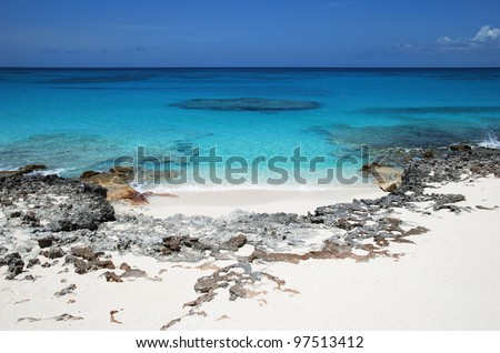 The view of pristine rocky beach with crystal clear water of Caribbean Sea (Half Moon Cay, The Bahamas). - stock photo