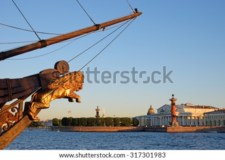 The view of the arrow of Vasilevsky island on the background of the wooden nose of the ship, decorated with a gold lion on a Sunny summer day in St. Petersburg - stock photo