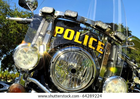 The view of the front end of a Police motorcycle parked at the station. Lights, blinkers and emergency flashers are all seen in this fully customized, two wheeled law enforcement bike. - stock photo
