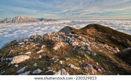 The view of the mountains above the clouds from the Srednji vrh mountain with the Kamnik-Savinja Alps in the background at dusk, Slovenia - stock photo