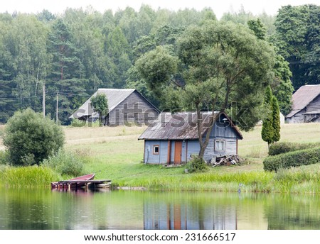 The view of the old wooden bathhouse under the tree in Lithuanian countryside. - stock photo