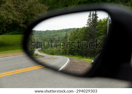 The view of windy roads in Cape Breton when viewed from a car wing mirror - stock photo