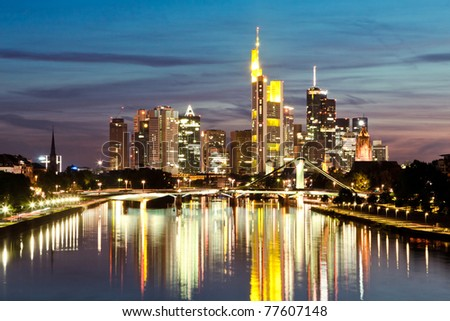 The view on Frankfurt skyline at night with reflection in the water - stock photo