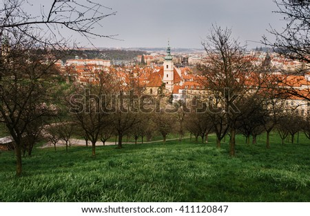 The View on the Prague's old town with flowering trees and grass - stock photo