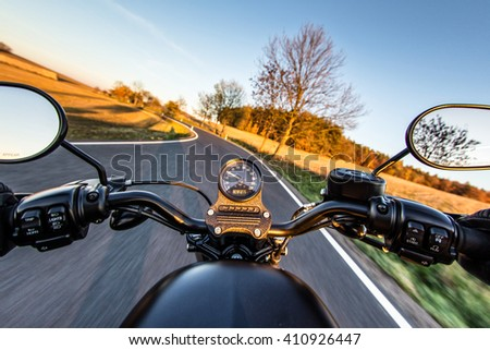 The view over the handlebars of a speeding motorcycle - stock photo
