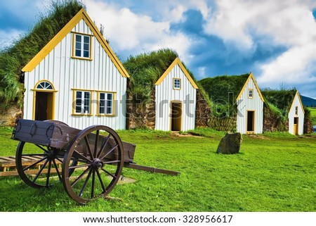 The village first settlers in Iceland. The reconstituted village - Pioneer Museum - Viking. Old wooden two-wheeled carriage on front lawn of the house - stock photo