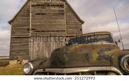 The vintage rusted car and old wooden barn scene. - stock photo