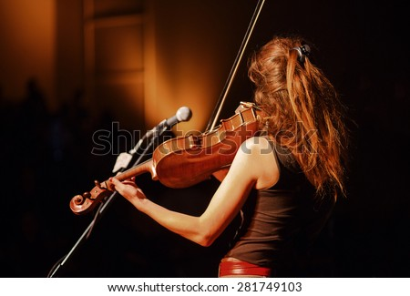 The violin player performing in the hall - stock photo