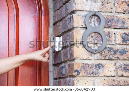 The visitor hand presses the bell at the door - stock photo