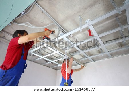 The wage workers set the ceiling profile in the new flat - stock photo