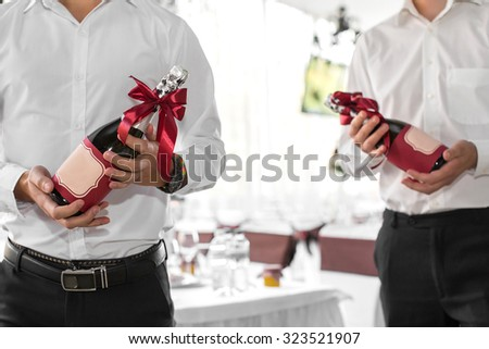 the waiter holds a bottle of champagne - stock photo