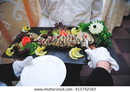 The waiter places a pike on a plate - stock photo