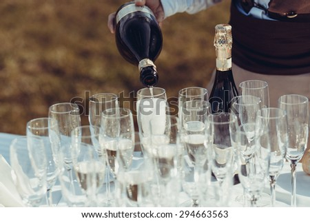 The waiter pours champagne in crystal glasses - stock photo
