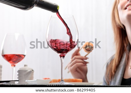 The waiter pours wine into a glass for a woman eating maki with chopsticks on a background - stock photo